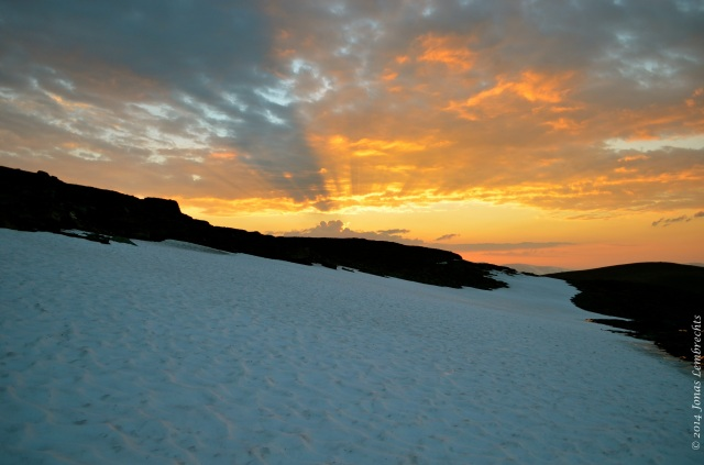 Midnight sun above snow patch