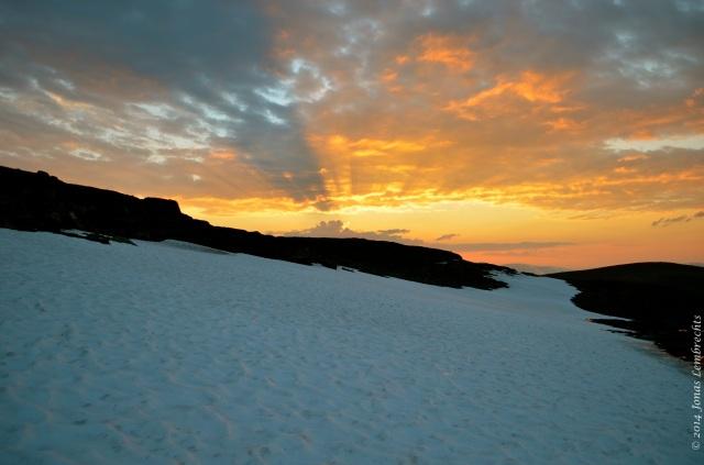Midnight sun above snow patch
